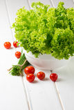 Lettuce salad, tomatoes and green onion on white background. Lettuce salad in wihte bowl, tomatoes and green onion on wooden white background stock photography