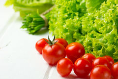 Lettuce salad, tomatoes and green onion on white background. Lettuce salad, tomatoes and green onion on wooden white background royalty free stock photos