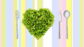 Lettuce in the shape of heart on colored tablecloth with cutlery Royalty Free Stock Photo
