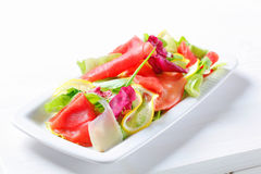 Lettuce with thin slices of lemon and raw beef Royalty Free Stock Images