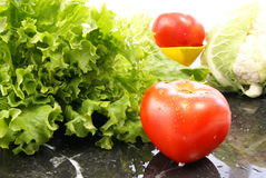 Lettuce and Tomato. Fresh lettuce and ripe tomatoes on black marble cutting board Royalty Free Stock Images