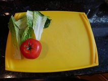 Lettuce and tomato on cutting board. Lettuce and tomato on yellow cutting board royalty free stock images