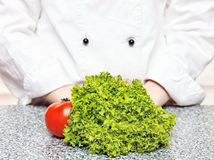 Lettuce and tomato in front of the chefs Royalty Free Stock Photography