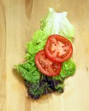 Lettuce and tomatoe. Lettuce and sliced tomatoes on wood cutting board Royalty Free Stock Photography