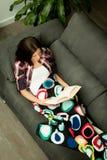 Lettura abbastanza castana della ragazza sul sofà Fotografia Stock Libera da Diritti