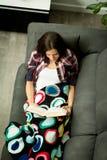 Lettura abbastanza castana della ragazza sul sofà Fotografie Stock