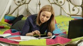 Lettura amichevole della studentessa sulla compressa digitale che si trova a letto Istruzione online della bella donna nella casa video d archivio
