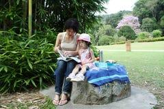Lettura asiatica del daugther e della madre al giardino Immagine Stock