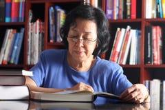 Lettura asiatica maggiore della signora nella libreria Immagini Stock