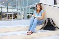 Lettura attraente della donna alla libreria di banco Fotografia Stock