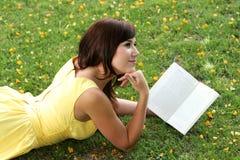 Lettura attraente della ragazza del Brunette all'aperto Fotografie Stock