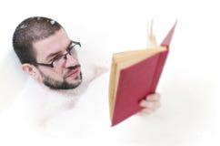 Lettura barbuta dell'uomo nella vasca Fotografie Stock Libere da Diritti