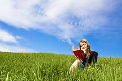 Lettura bionda sull'erba Fotografia Stock