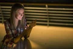 Lettura contentissima della giovane donna sms sul suo sorridere del telefono cellulare Fotografie Stock Libere da Diritti