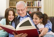 Lettura dei bambini e dell'anziano Immagine Stock Libera da Diritti