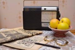 Lettura dei giornali sovietici vecchi, radio d'annata Fotografia Stock