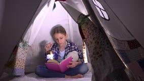 Lettura del bambino, bambino che studia nella notte, ragazza che gioca nella stanza dei giochi, imparante in tenda stock footage