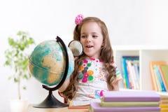 Lettura del bambino con lo sguardo della lente d'ingrandimento il globo Fotografie Stock