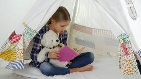 Lettura del bambino, studiante nella stanza dei giochi, bambino che gioca al campo da giuoco, imparante ragazza video d archivio