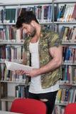 Lettura del culturista dal libro in una biblioteca Immagine Stock Libera da Diritti