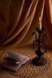 Lettura del libro dall'indicatore luminoso di una candela. Fotografie Stock Libere da Diritti