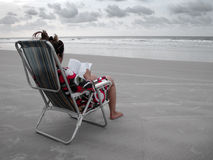 Lettura del libro nella spiaggia Immagine Stock