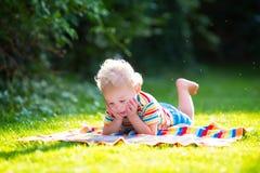 Lettura del ragazzino nel giardino di estate Fotografia Stock