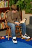 Lettura del ragazzo nella libreria Immagine Stock