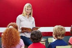 Lettura dell'insegnante dal libro nella classe Fotografia Stock