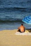 Lettura dell'uomo alla spiaggia Immagine Stock Libera da Diritti