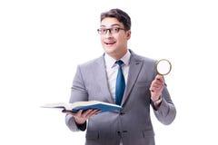 Lettura dell'uomo d'affari con la lente d'ingrandimento isolata sulla parte posteriore di bianco Immagini Stock Libere da Diritti