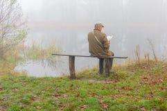Lettura dell'uomo sulla sponda del fiume Immagini Stock