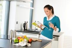 Lettura della casalinga della donna che cucina la cucina di ricetta del libro Fotografia Stock
