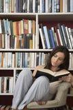 Lettura della donna contro gli scaffali per libri a casa immagini stock