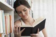 Lettura della donna dagli scaffali per libri a casa immagini stock