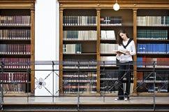 Lettura della donna davanti allo scaffale per libri Fotografia Stock