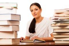 Lettura della donna dietro la tavola fra il mucchio due dei libri Immagini Stock