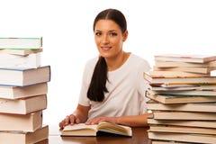 Lettura della donna dietro la tavola fra il mucchio due dei libri Immagine Stock