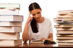 Lettura della donna dietro la tavola fra il mucchio due dei libri Fotografia Stock Libera da Diritti
