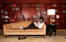 Lettura della donna nella libreria Fotografia Stock Libera da Diritti