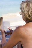 Lettura della donna sulla spiaggia Fotografia Stock Libera da Diritti