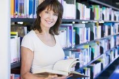 Lettura della donna in una libreria Fotografia Stock