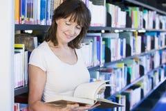 Lettura della donna in una libreria Fotografie Stock