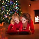 Lettura della figlia e della madre al posto del fuoco sulla notte di Natale Fotografia Stock