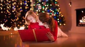 Lettura della figlia e della madre al posto del fuoco sulla notte di Natale Immagine Stock Libera da Diritti