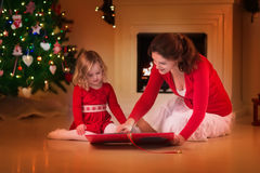 Lettura della figlia e della madre al posto del fuoco sulla notte di Natale Immagine Stock