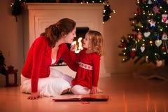 Lettura della figlia e della madre al posto del fuoco sulla notte di Natale Fotografie Stock