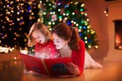 Lettura della figlia e della madre al posto del fuoco sulla notte di Natale Fotografia Stock Libera da Diritti