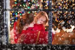 Lettura della figlia e della madre al posto del fuoco sulla notte di Natale Fotografie Stock Libere da Diritti