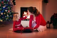 Lettura della figlia e della madre sulla notte di Natale al posto del fuoco Fotografie Stock